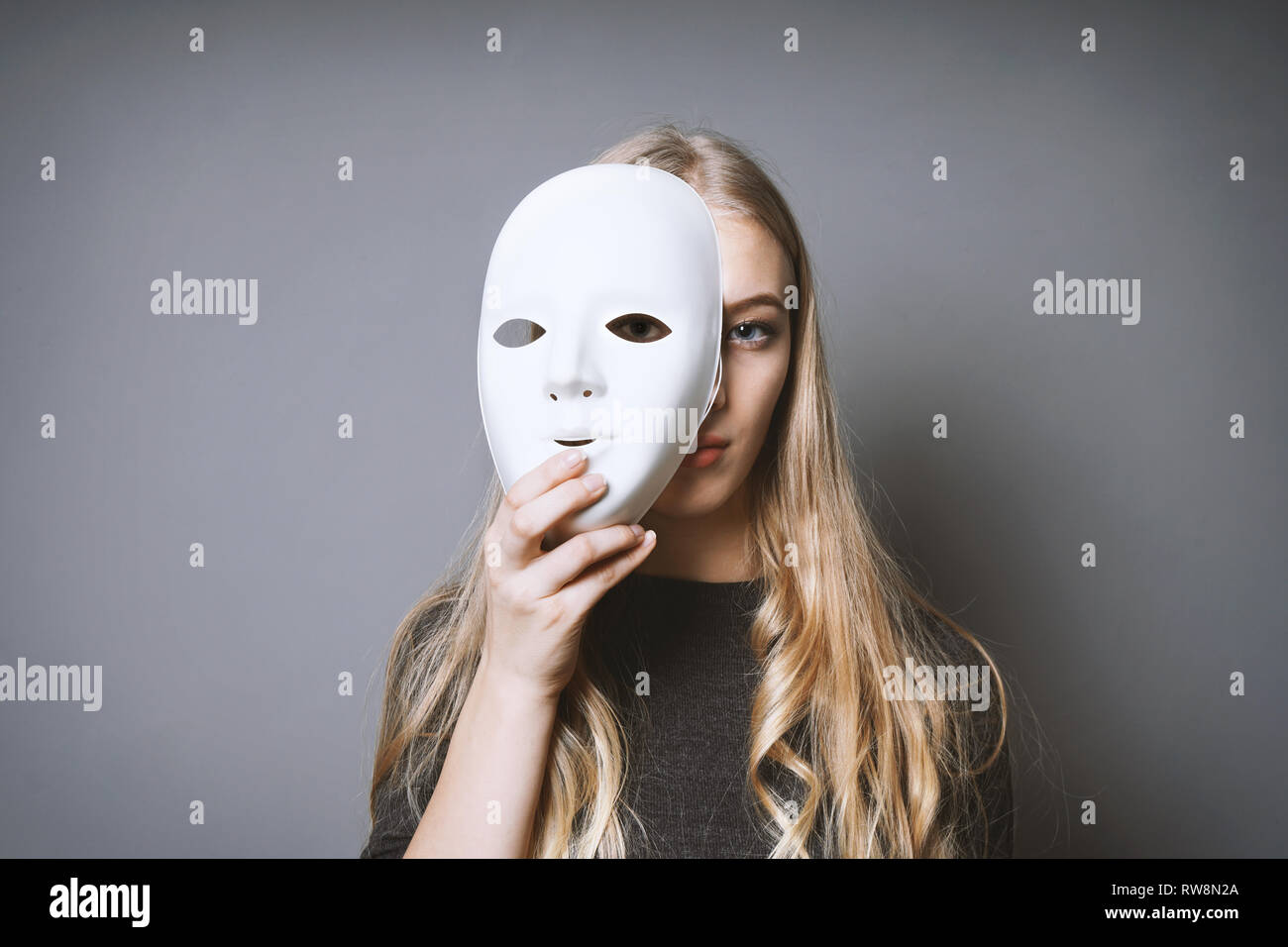 teen girl hiding her face behind mask - identity or personality concept Stock Photo