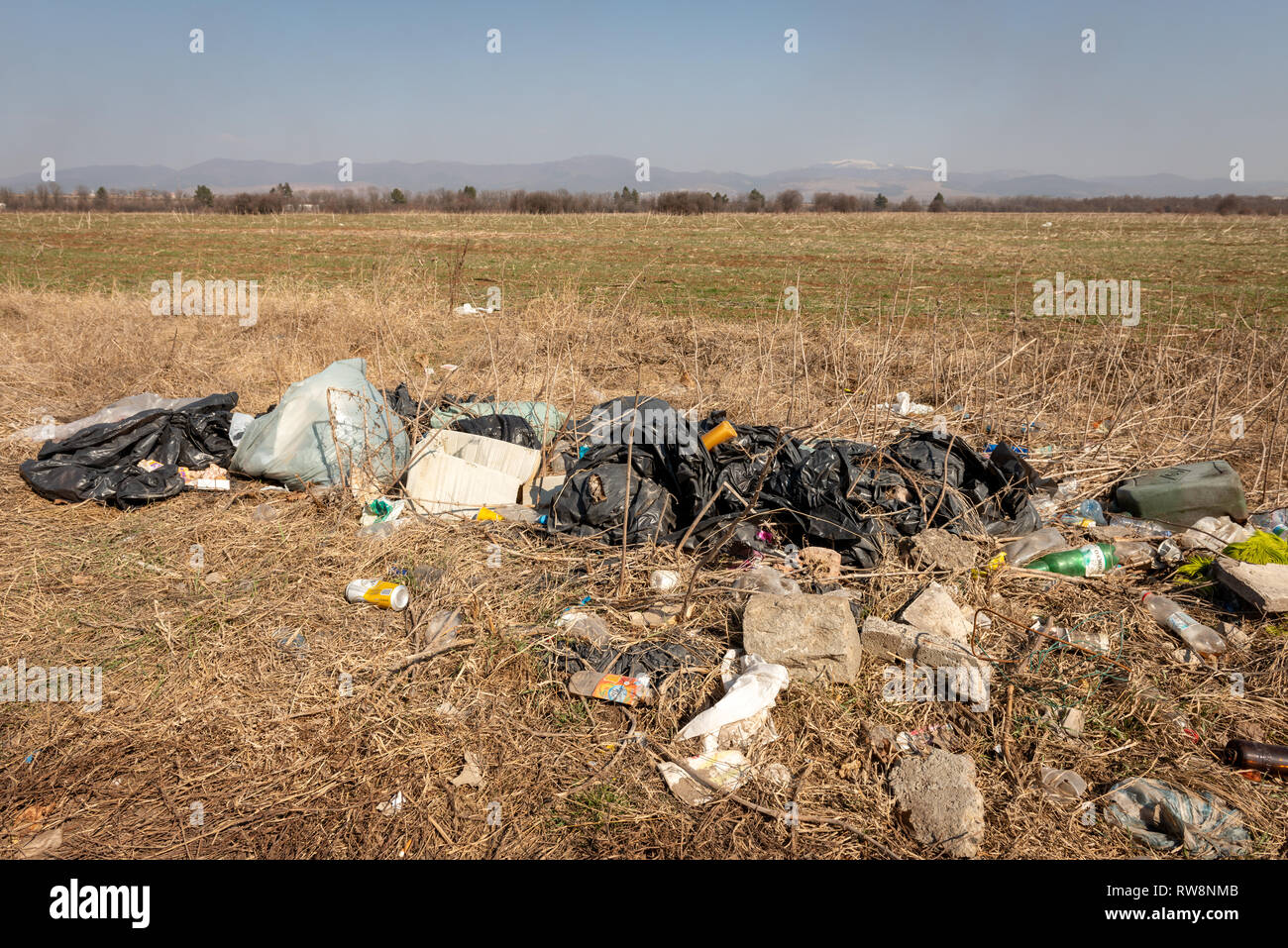 Dumped garbage waste litter on a field in bright sunny day. Typical view in the Bulgarian countryside. Environmental problem. - Stock Image