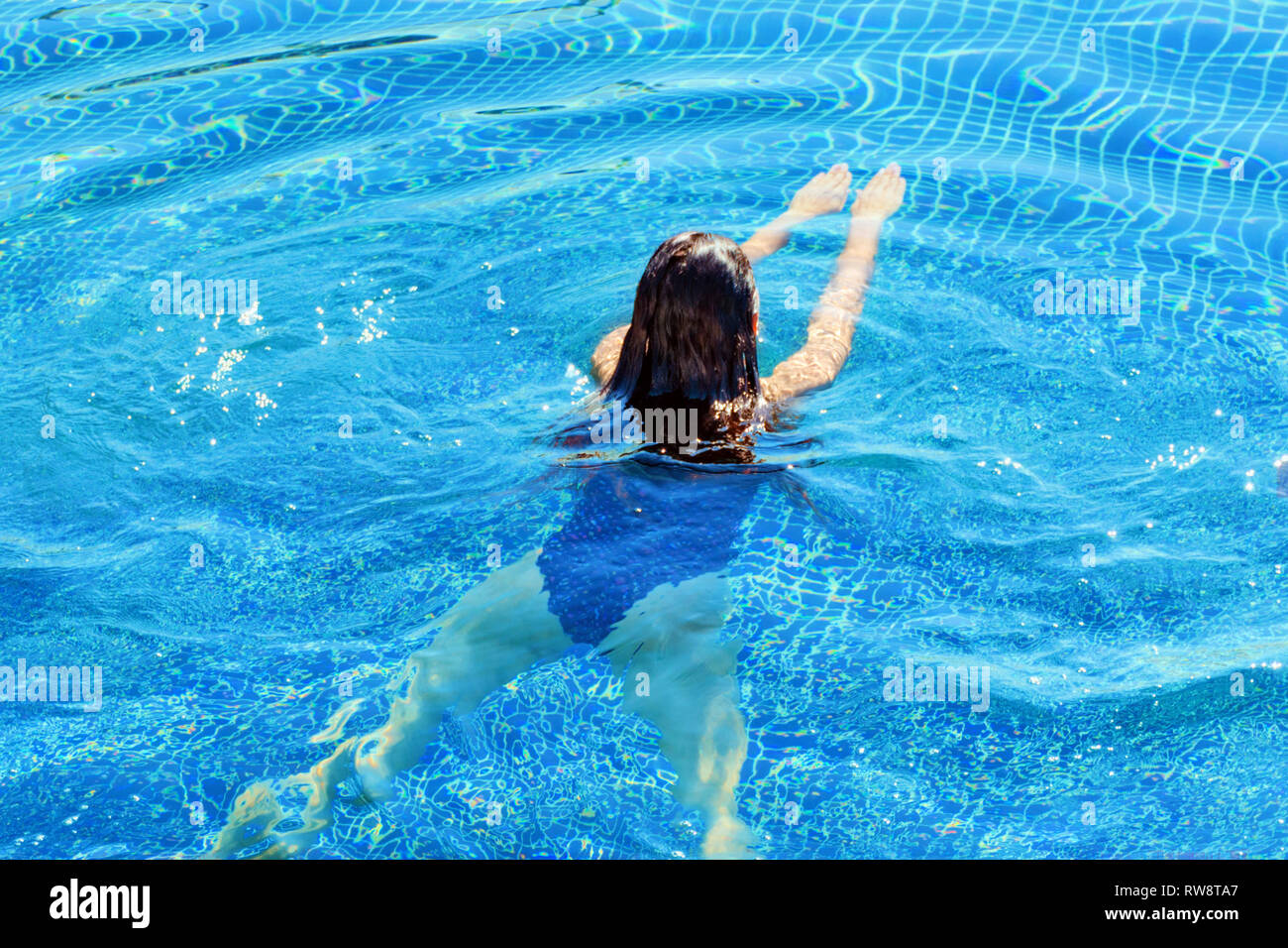 Rear view of a woman swimming. Swim and fitness Stock Photo