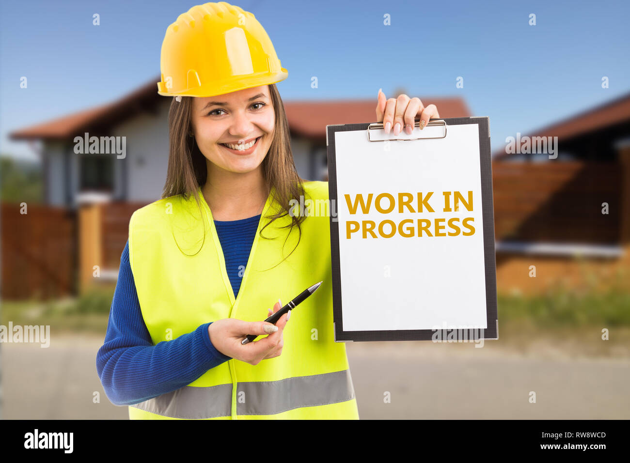 Woman builder with friendly expression holding work in progress orange text on clipboard pointing by using pen - Stock Image