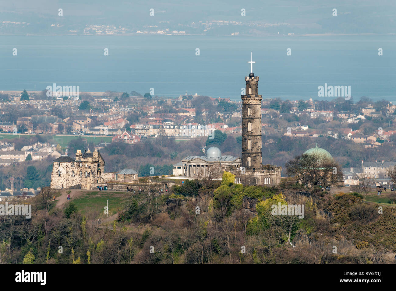 The Nelson Monument on Calton Hill photographed from Salisbury Crags on a sunny day, Edinburgh, Scotland Stock Photo