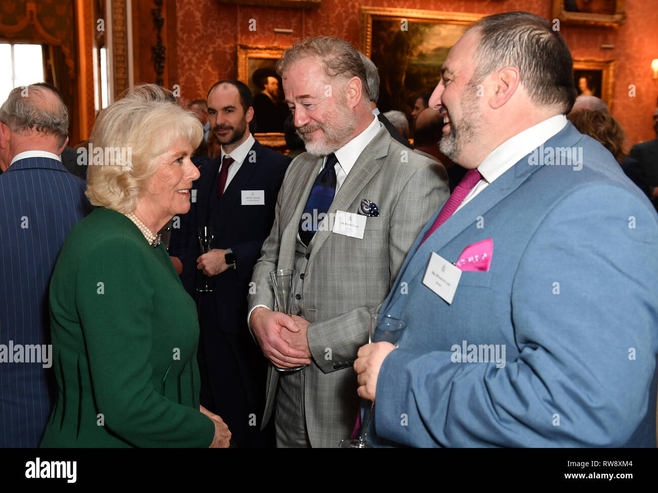 The Duchess of Cornwall speaks with actor Owen Teale and singer Wynne Evans (right) at a reception at Buckingham Palace in London to mark the fiftieth anniversary of the investiture of the Prince of Wales. - Stock Image