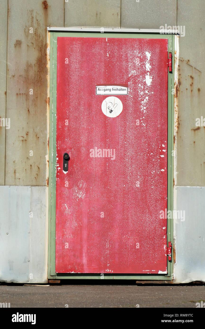 Rote alte Metalltür an einem Hafenschuppen - Stock Image