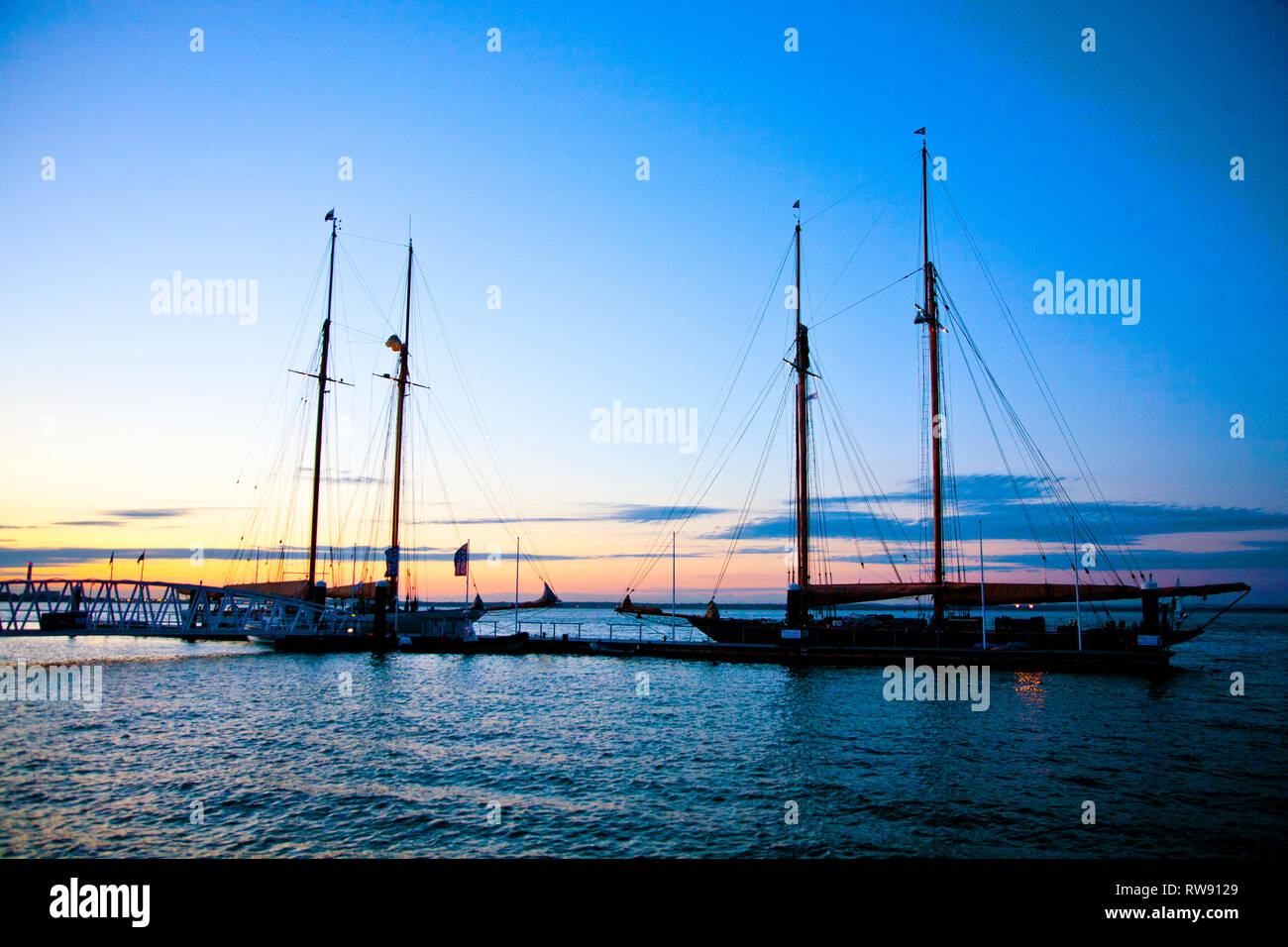 seafront, masts, Royal Yacht Squadron, Parade, Trinity, Landing, stage, pontoon, sunset, silhouette, yacht, gaffer, Cowes, Isle of Wight, - Stock Image