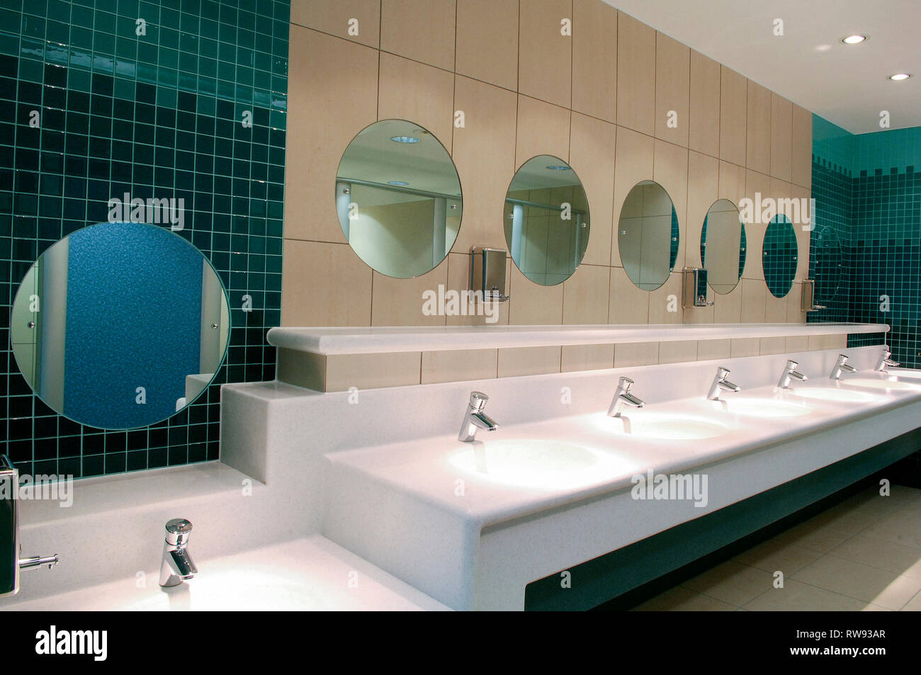 Rows of sinks and mirrors in a public restroom - Stock Image