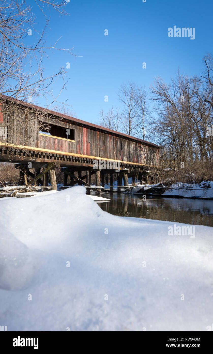 The Clarence covered bridge in Decatur, Wisconsin, on a cold winters day with blue skies and snow. - Stock Image