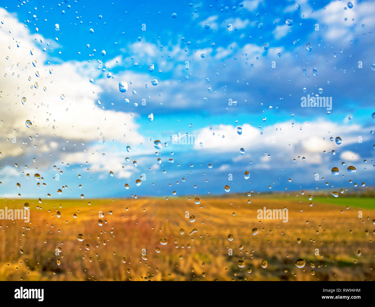 Blurred cloudy sky and cultivated fields seen through a wet car window covered with rain drops with image reflections within - Stock Image