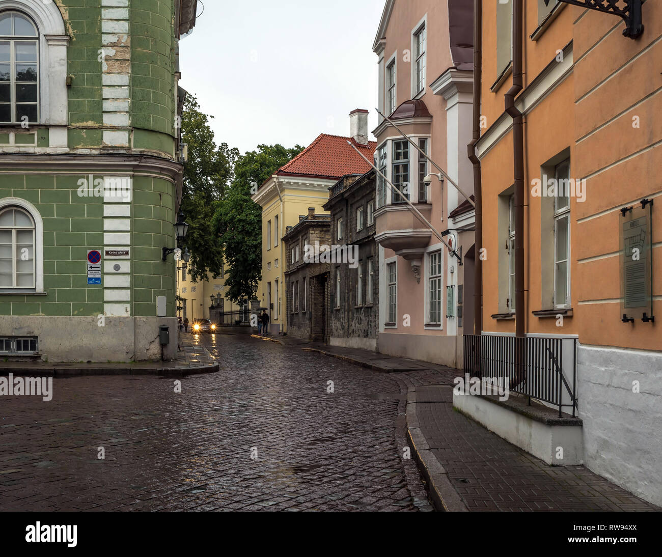 Tallinn old city street in dull, murky rainy evening, with grey sky and wet cobblestone road. Old green, pink and orange buildings in the Old Tallinn, - Stock Image