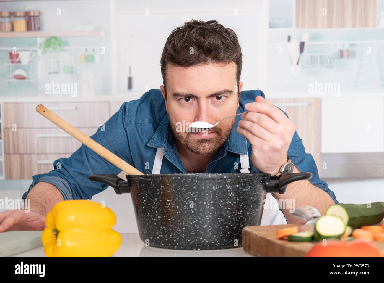One man is cooking in his kitchen and adding ingredient Stock Photo