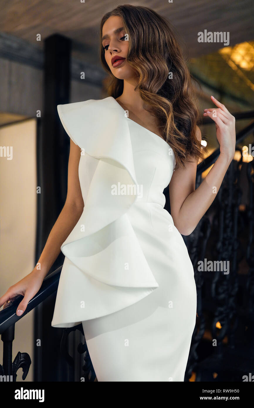 Gorgeous lady in designed white evening dress with open shoulder< standing on the stairs in the restaurant. Hand on the curly volume hair, beautiful Stock Photo
