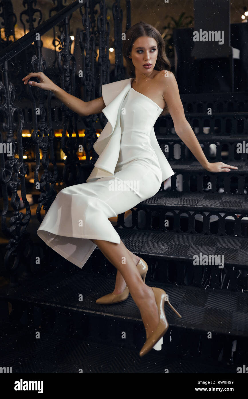 Modern elegant white dress with one open shoulder and beige heel shoes. Tender lady sitting on the black steps in restaurant, put hand on the handrail Stock Photo