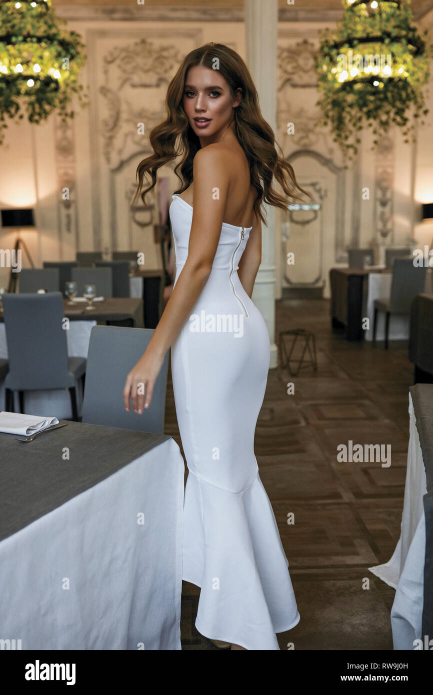 Tall slim model in white long dress and open shoulders shooting on restaurant, standing near the table. Bright makeup and waving stylish hair. Green Stock Photo
