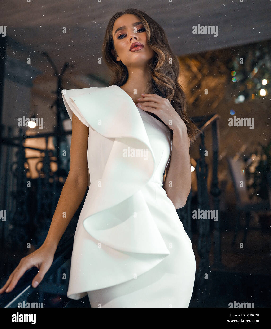 Pretty young model with curly hairstyle and makeup wearing the white modern dress, open arms and shoulder. Posing for the fashion magazine, shooting Stock Photo