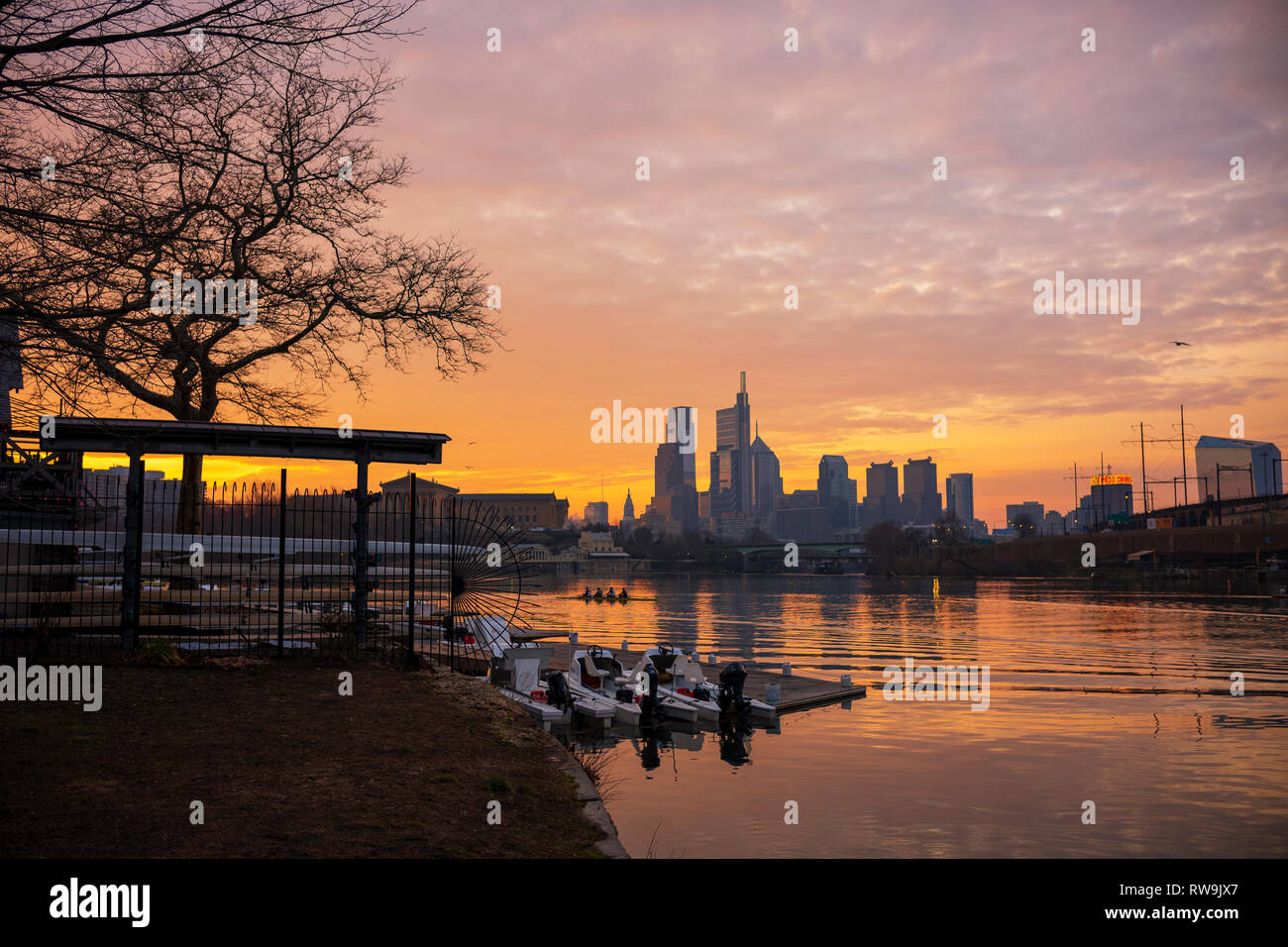 Crew members practice on the Schuylkill River in Philadelphia, Pennsylvania, seen here from Boathouse Row at sunrise. - Stock Image