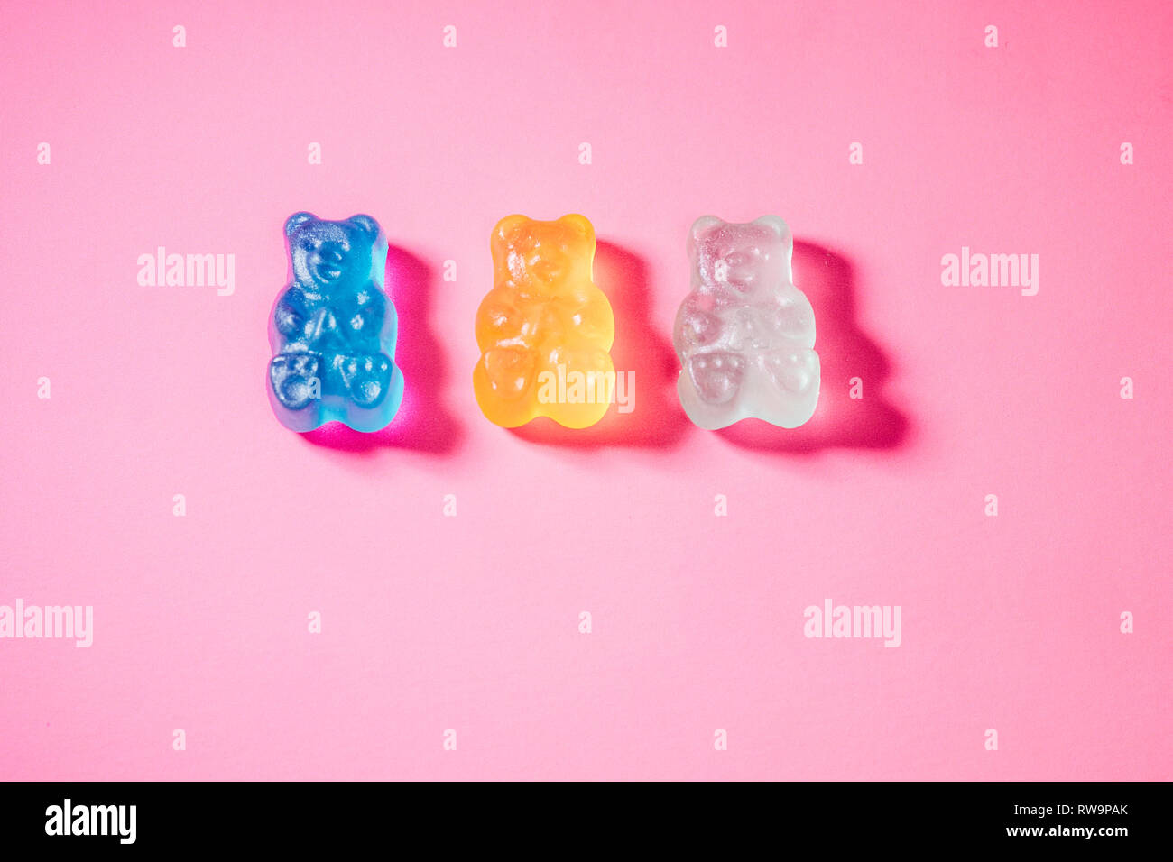A close-up of three brightly-colored gummy bears, photographed on a pink background with poppy studio light. Stock Photo