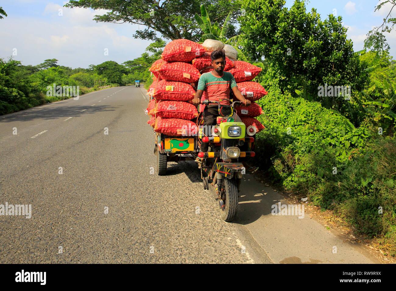 Sacks of onion loaded on the locally assembled tricycle called Nachimon on the Faridpur-Gopalganj highway. Faridpur, Bangladesh. Stock Photo