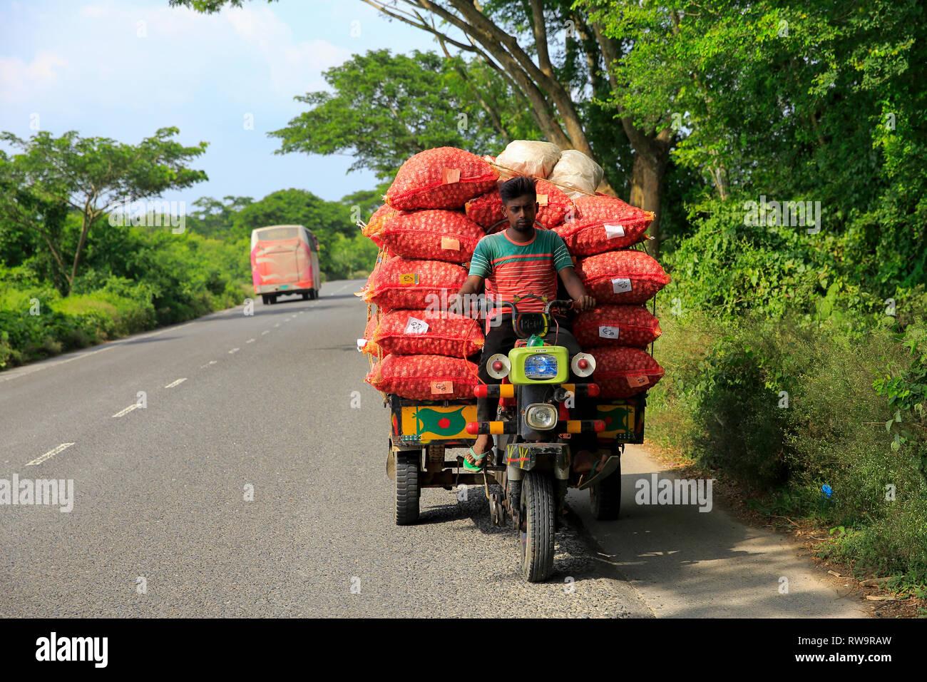 Sacks of onion loaded on the locally assembled tricycle called Nachimon on the Faridpur-Gopalganj highway. Faridpur, Bangladesh. - Stock Image