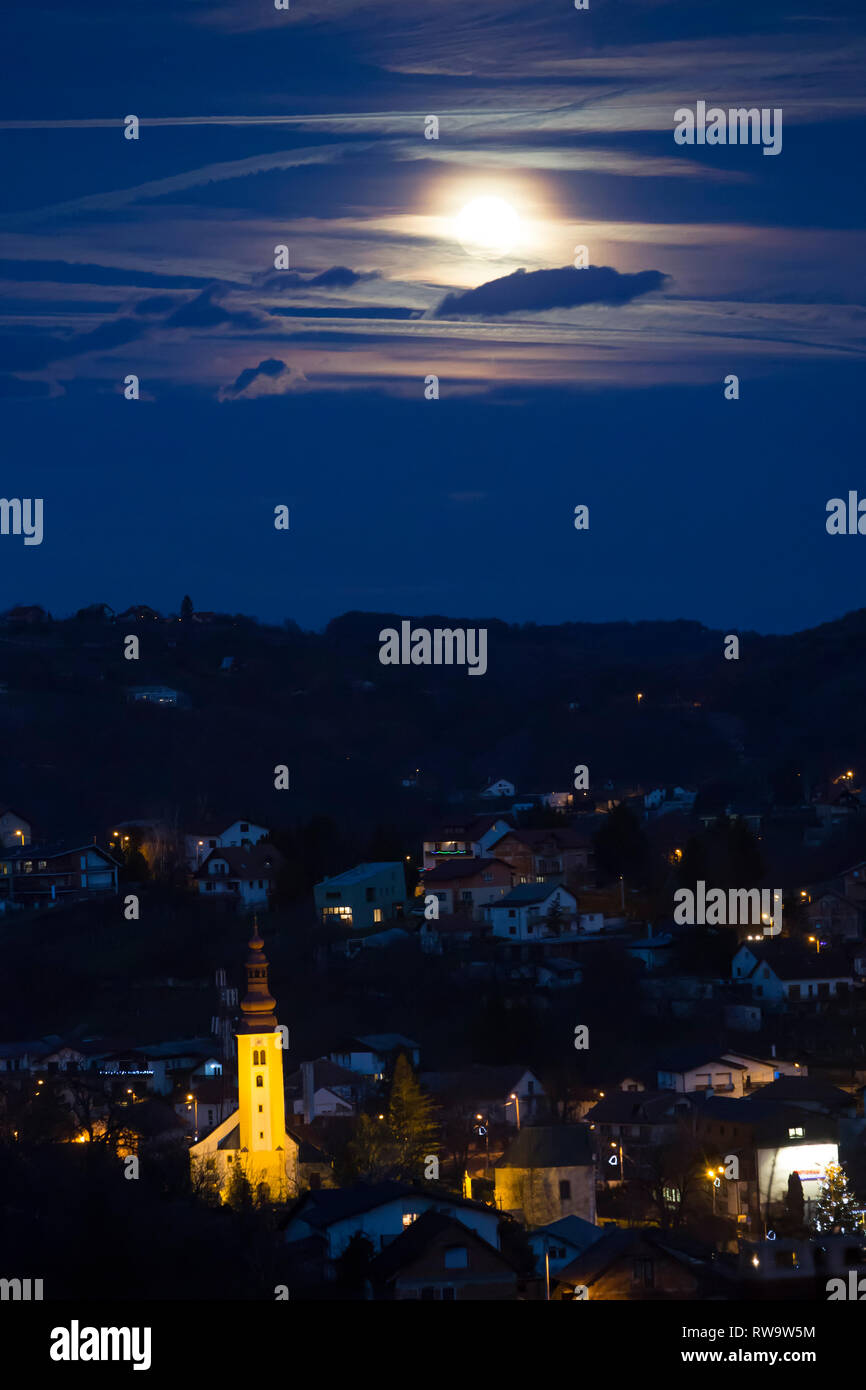 Church in the village with full moon at night - Stock Image