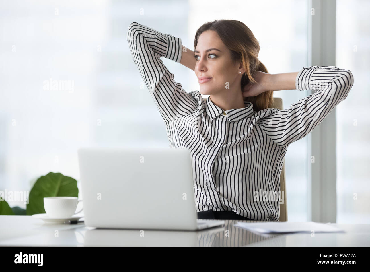 Happy businesswoman holding hands behind head finished resting at workplace - Stock Image