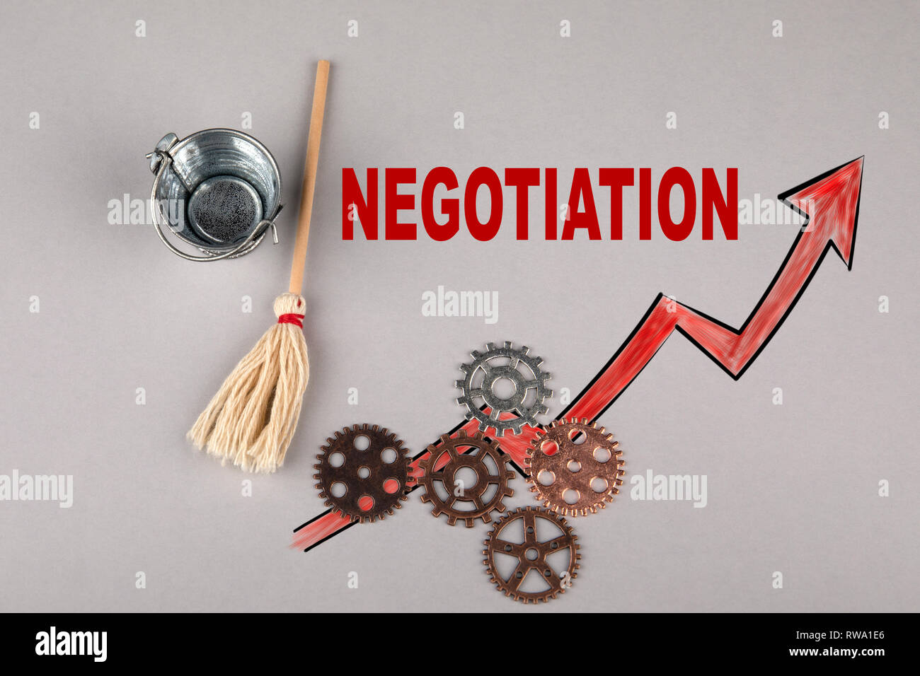 Negotiation concept. Gears, bucket with a broom - Stock Image