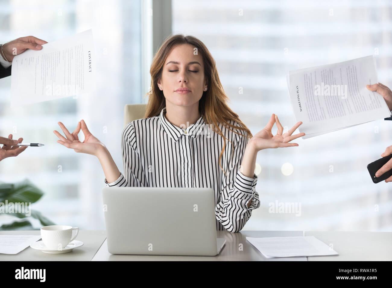 Calm female executive meditating taking break avoiding stressful job - Stock Image
