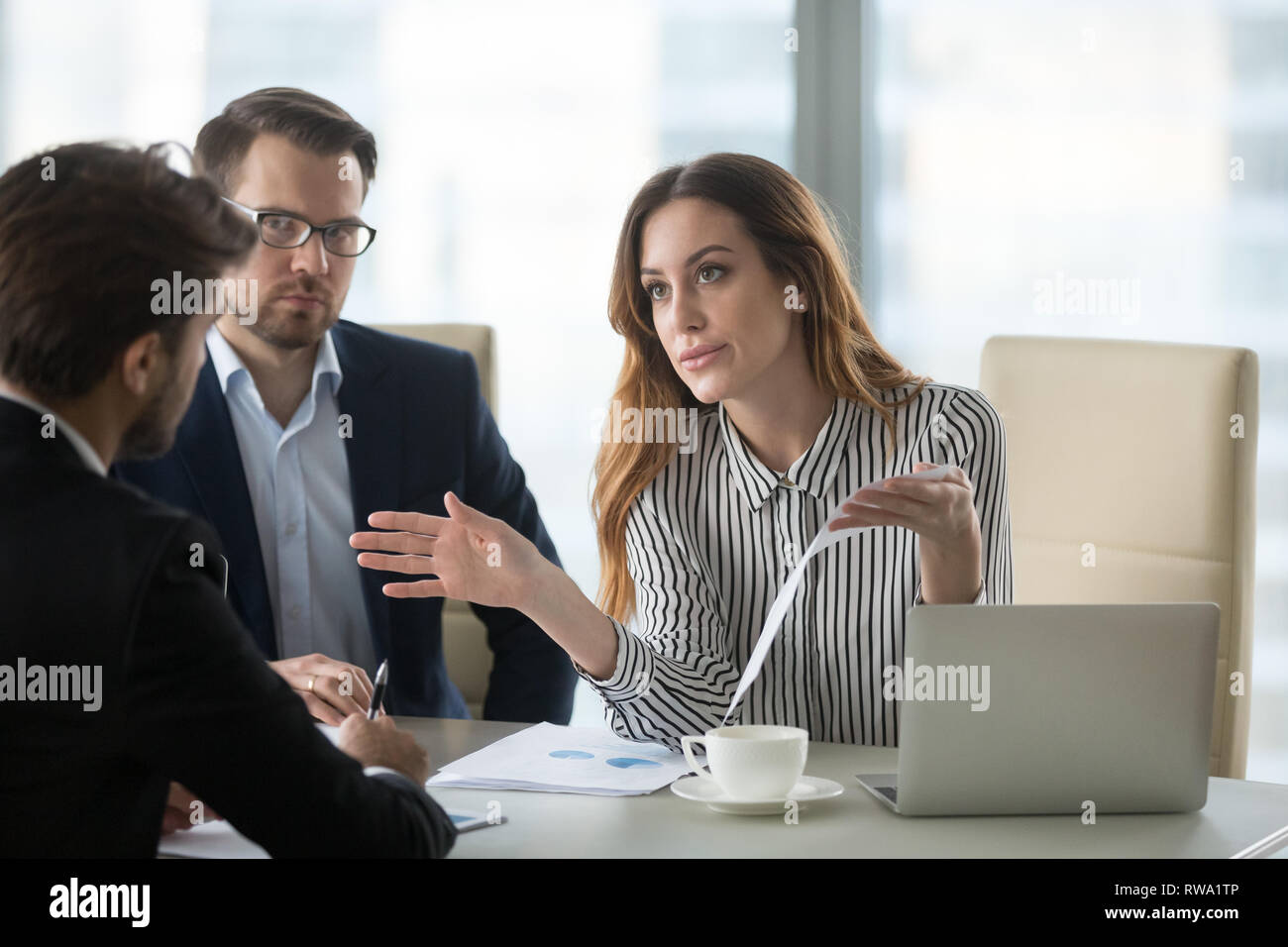 Dissatisfied executive having conflict with employee about financial report mistake - Stock Image