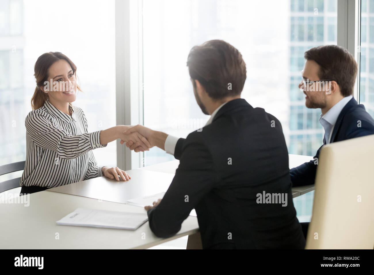Confident female job applicant shaking hand of hr recruiting manager Stock Photo