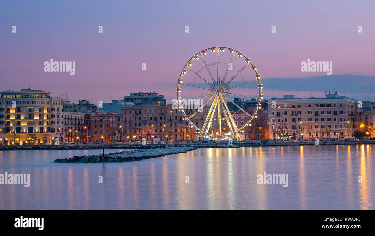Panoramic Night view of Illuminated giant Ferris wheel on the waterfront of Bari, region of Apulia, Italy. Puglia. Panorama - Stock Image