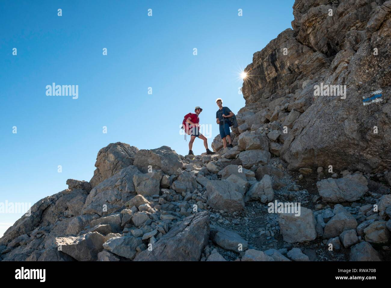 Two hikers ascending to the Hochvogel, Sonnenstrahlen, Allgäu, Allgäuer Hochalpen, Bavaria, Germany - Stock Image