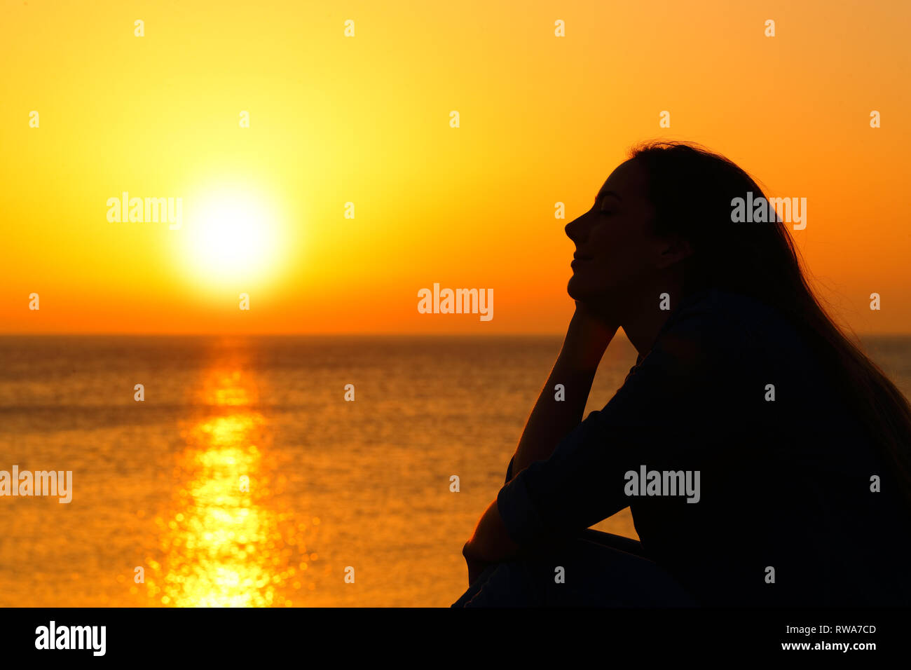 Side view portrait of a woman silhouette watching sun at sunset on the beach Stock Photo