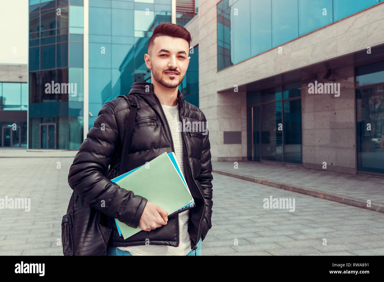 Arabian student holding copybooks by modern university outside. Young happy man with backpack looking at camera - Stock Image