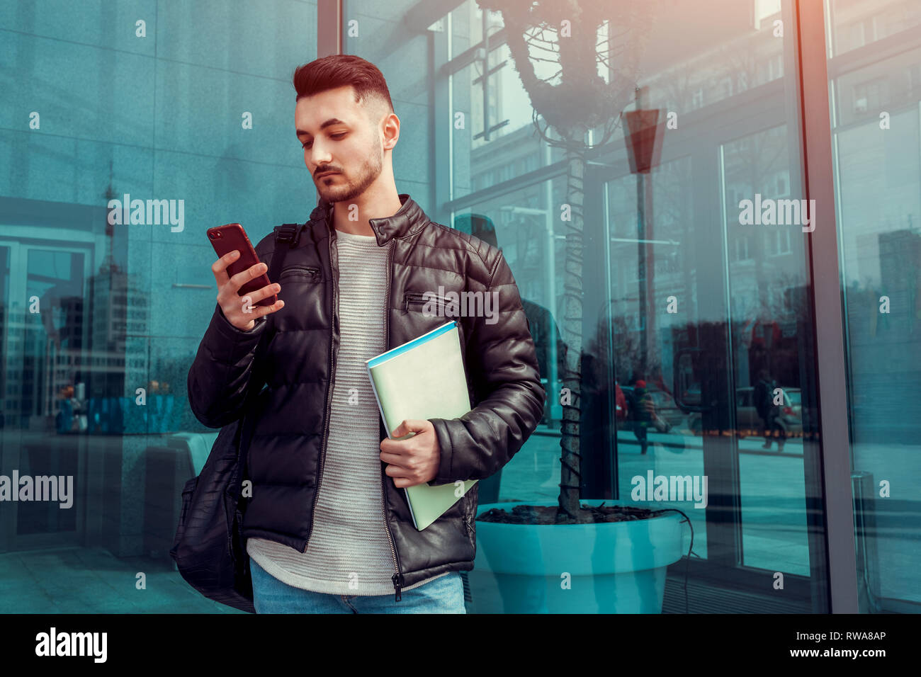 Confident arabian student using smartphone outside. Serious guy looks at phone in front of modern building after classes. Man holds copybooks. Educati - Stock Image