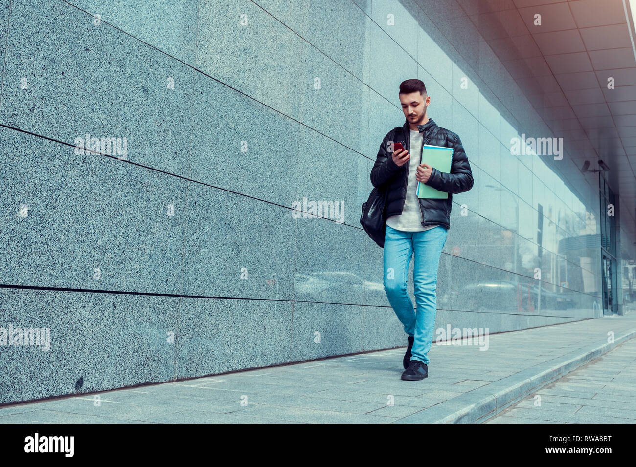 Serious arabian student using smartphone in city center. Young man hurrying up to university. - Stock Image