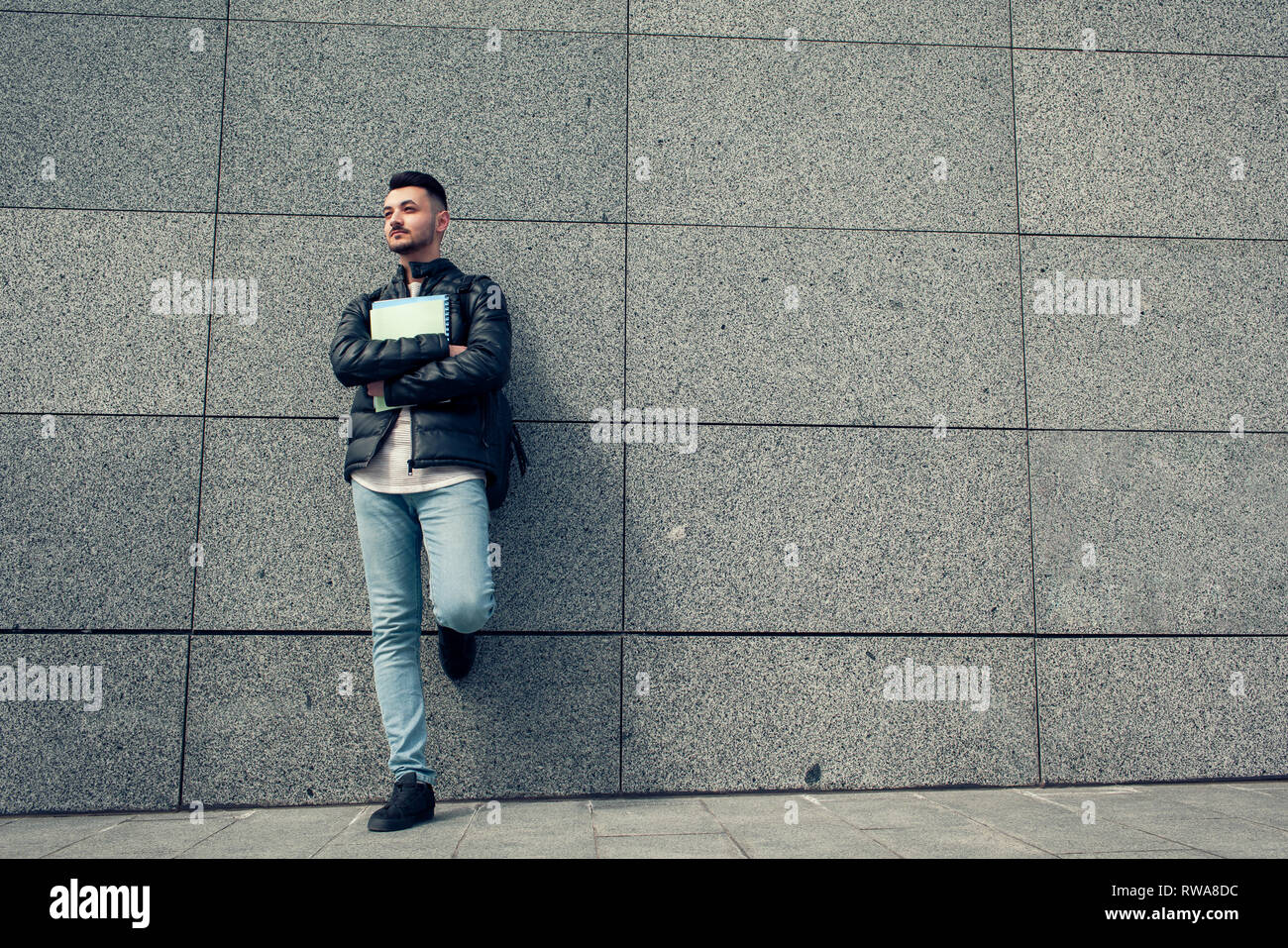 Arabian student holding copybooks by the wall outside. Young man with backpack waiting for groupmates - Stock Image