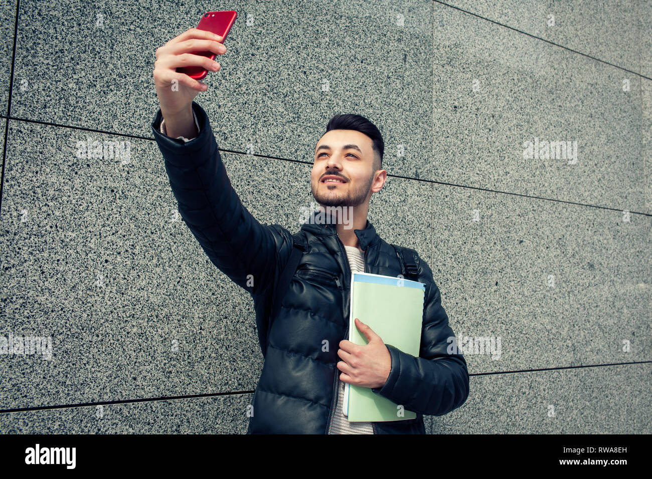 Arabian student takes selfie on smartphone outside. Happy guy looks at phone by the wall after classes. Man holds copybooks - Stock Image