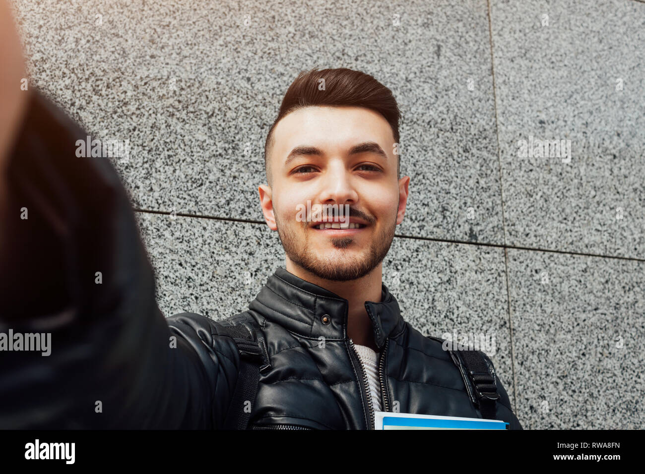 Arabian student takes selfie on smartphone outside. Happy guy looks at phone by the wall after classes. Man holds copybooks. Education - Stock Image