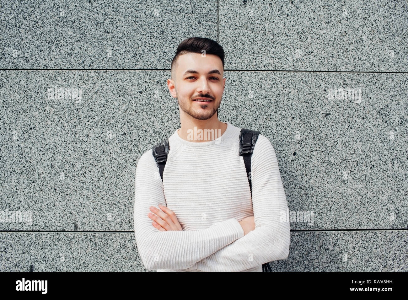 Arabian student with backpack standing by stone wall outside. Young smiling man with crossed hands waiting for groupmates. - Stock Image