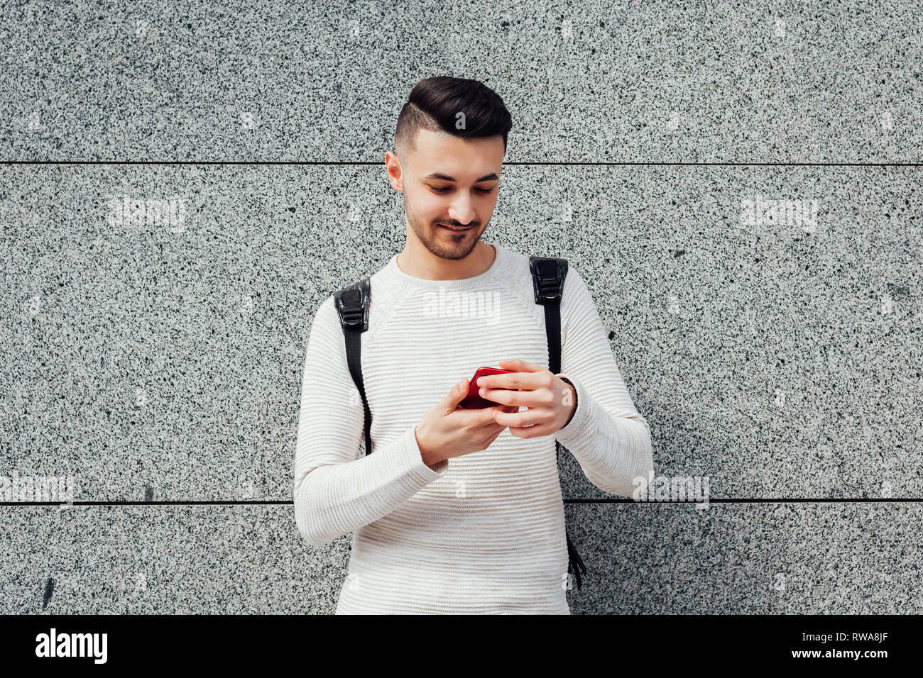 Arabian student with backpack using smartphone outside. Smiling man typing message by the wall after classes. Nowaday communication - Stock Image