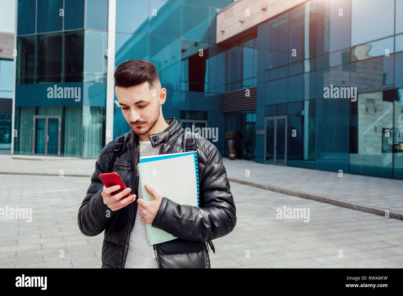 Happy arabian student using smartphone outside. Confident guy looks at phone in front of modern building after classes. Man holding copybooks - Stock Image