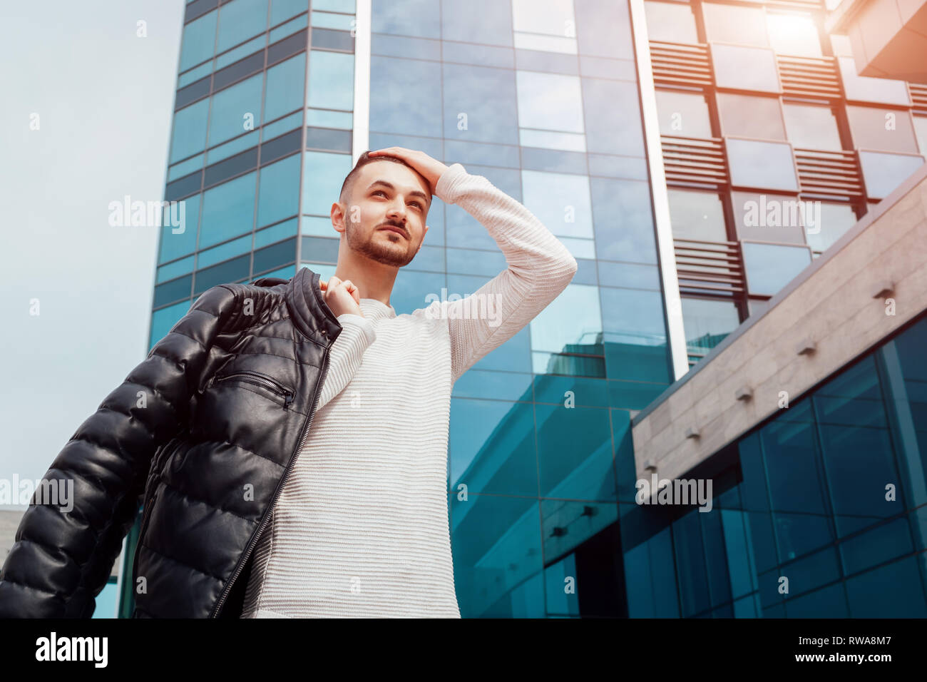 Arabian man holding his coat and walking in city center. Young man puts coat on shoulder. Stylish handsome hipster student - Stock Image