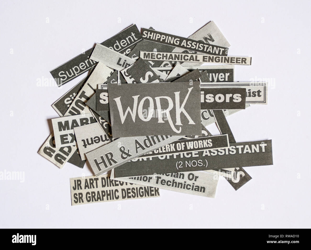 Jobs or careers concept: job titles or occupations cut off from newspaper and with Work on top of the pile - Stock Image