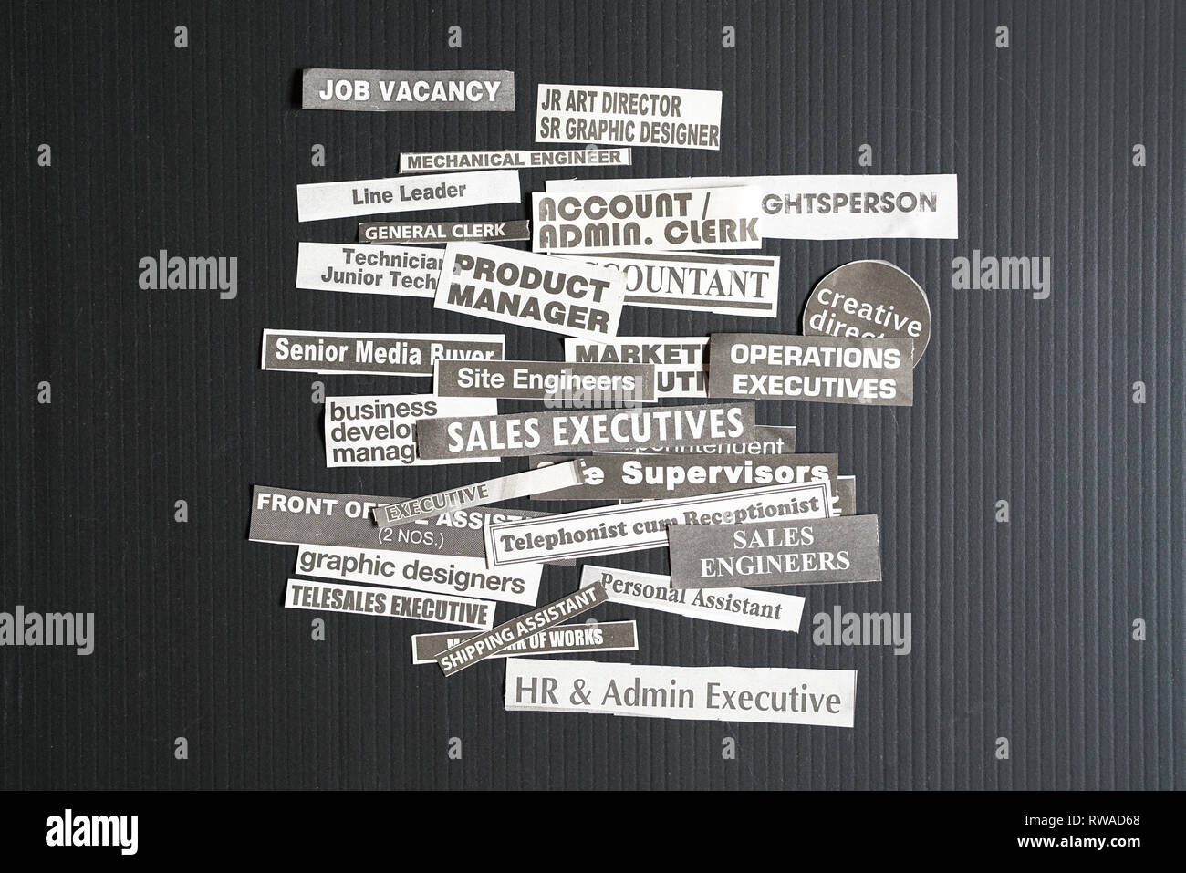 Jobs or careers concept: multiple job titles or occupations cut off from newspaper on black background - Stock Image