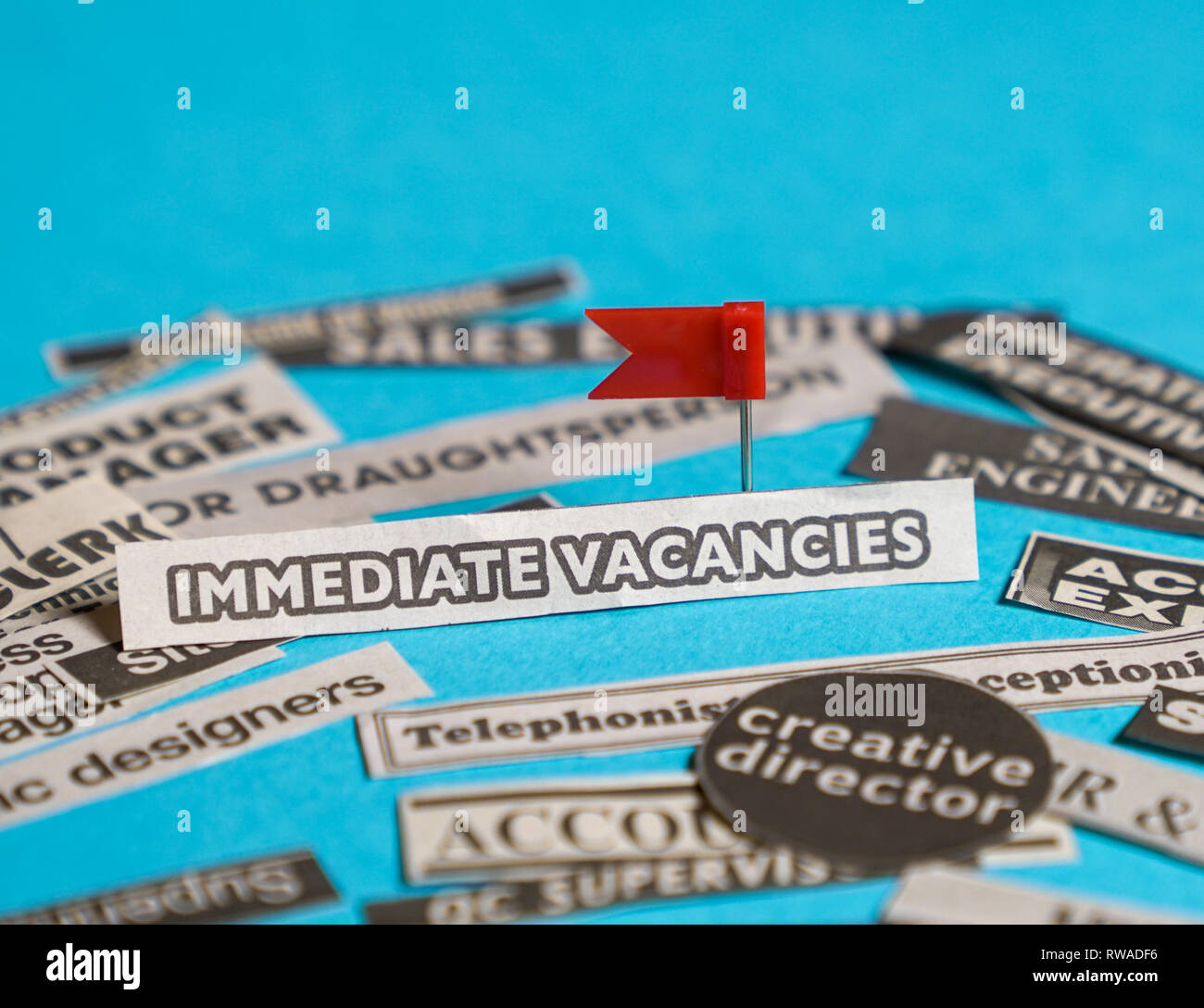 Jobs or careers concept: multiple job titles or occupations cut off from newspaper with Immediate Vacancies at the centre of the pile, blue background - Stock Image