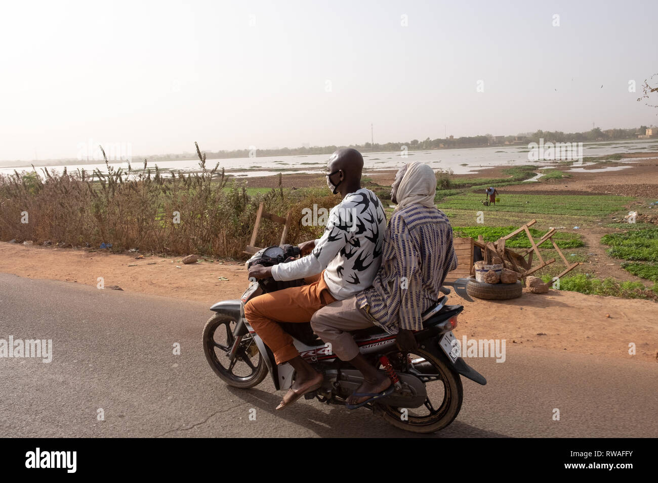 MA man and a woman ride on a motorcycle in Bobo-Dioulasso, a part of western Burkina Faso that is affected by insecurity and jihadist terrorism Stock Photo