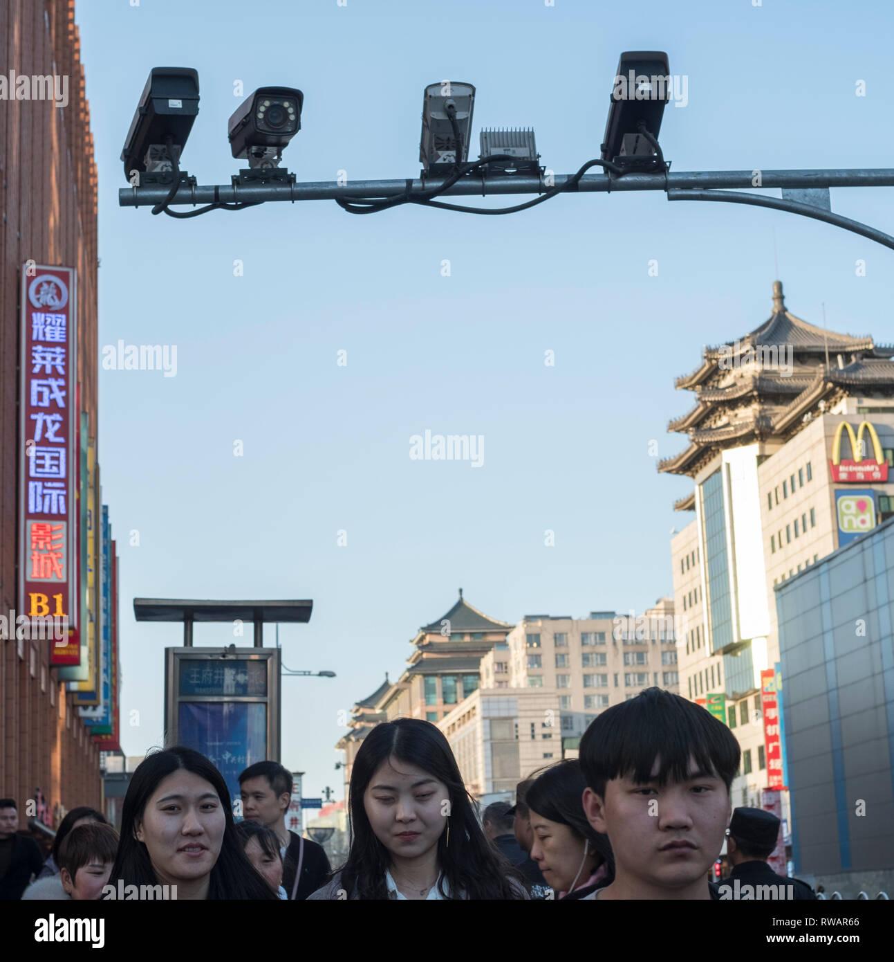 Pedestrians walk below CCTV cameras in Wangfujing Street in Beijing, China. 05-Mar-2019 - Stock Image