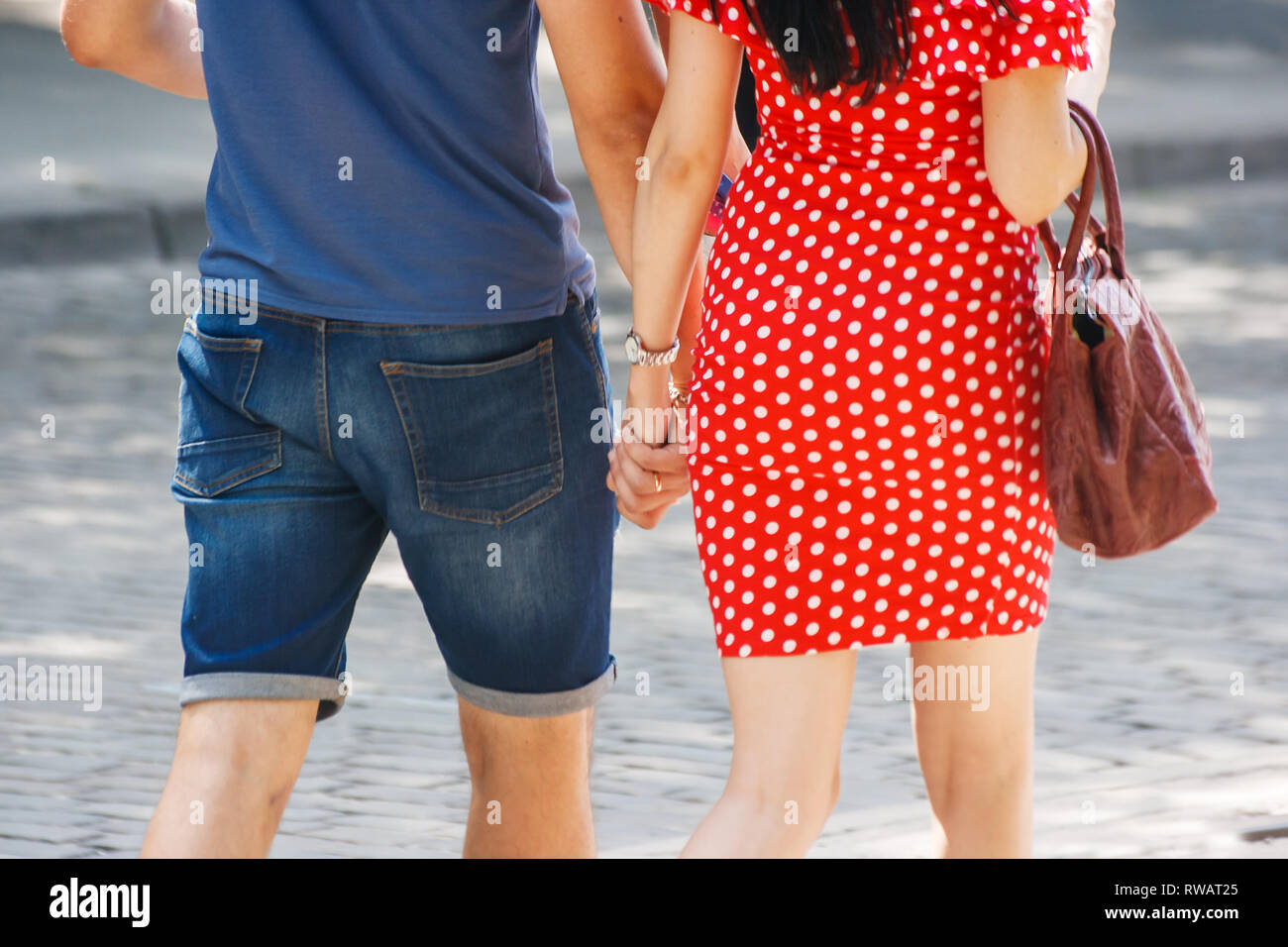 young couple walking down the street holding hands on sunny summer day Stock Photo