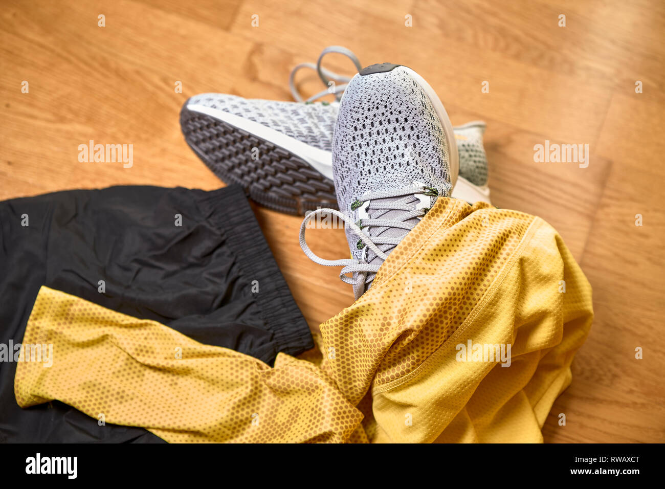 running shoes along with a shirt and shorts on a wooden gym floor Stock Photo
