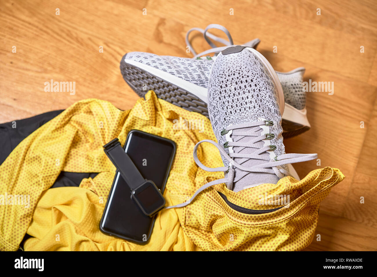 running shoes with a t-shirt, pants and technological accessories on a wooden gym floor Stock Photo