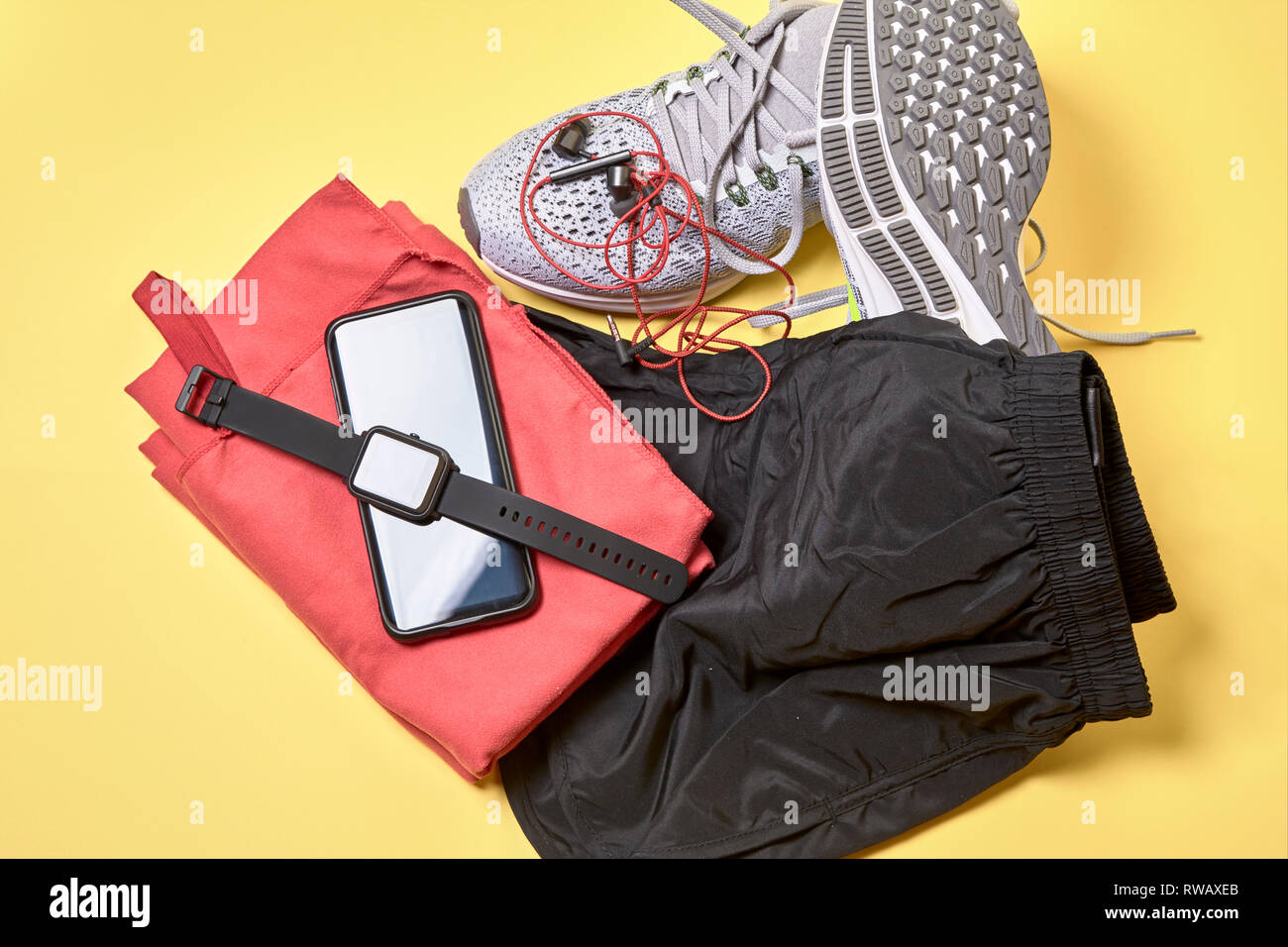running shoes with a pair of shorts, a red towel and technological accessories on a yellow background - Stock Image