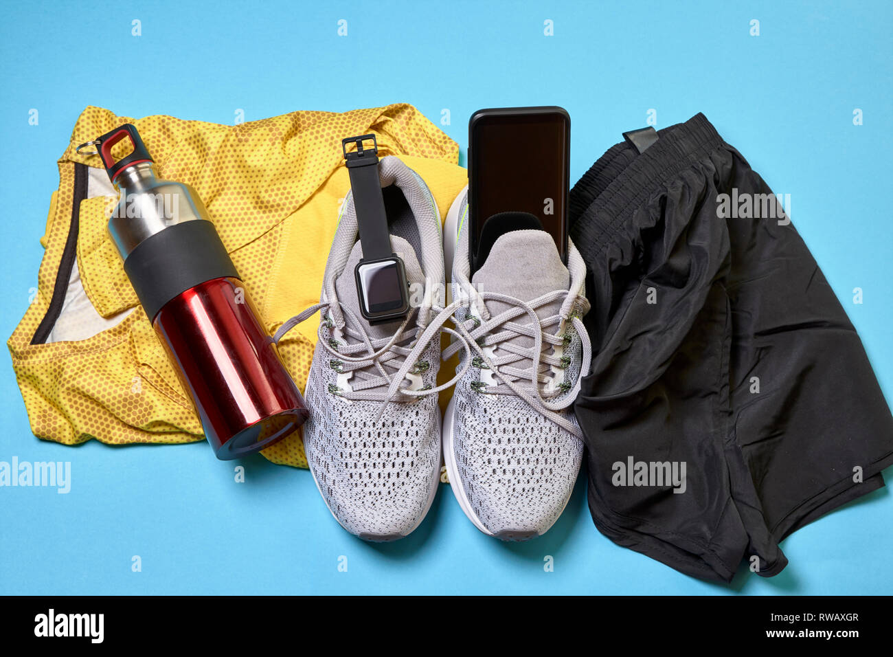 running shoes with a pair of shorts, a yellow shirt and technological accessories on a blue background - Stock Image